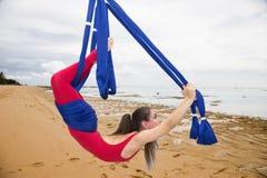 空中瑜伽或反地心引力的瑜伽 年轻女人实践的飞行瑜伽asana户外 库存图片