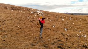空气视图 有一台照相机的女孩旅客在有背包和太阳镜的一个帽子走沿与黄色草的倾斜的 影视素材