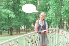 穿制服的女小学生认为 孩子遥远地学会 发展教育 免版税库存图片