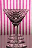 站在队中有白色和桃红色镶边背景的马蒂尼鸡尾酒和苦艾酒的四块空的玻璃 免版税库存照片