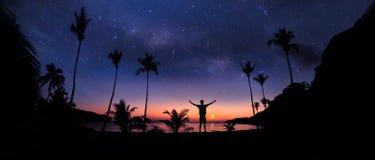 站立在与百万星和日出的椰子海滩的人全景风景 免版税库存图片