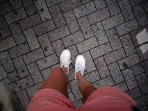 站立在岩石路面的女性腿顶视图在东京,日本 免版税库存照片