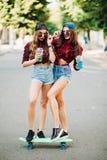 站立在滑板和摆在街道的赃物女朋友 库存照片
