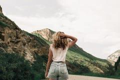 站立在高地的路的白色衣裳的时兴的女孩 绿草和山 免版税库存照片