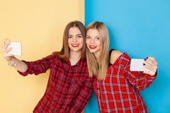 站立在黄色和蓝色墙壁的年轻愉快的妇女朋友画象  免版税库存图片