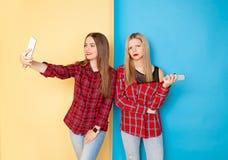 站立在黄色和蓝色墙壁的年轻愉快的妇女朋友画象  免版税图库摄影