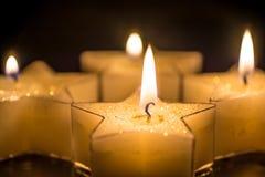第四出现的四个蜡烛在黑背景前面 免版税库存照片