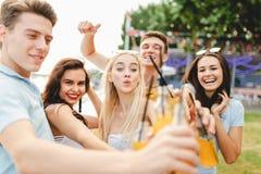 笑和喝黄色鸡尾酒和交往在美味的咖啡馆的悦目朋友公司在旁边 图库摄影
