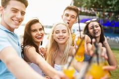 笑和喝黄色鸡尾酒和交往在美味的咖啡馆的悦目朋友公司在旁边 免版税库存照片