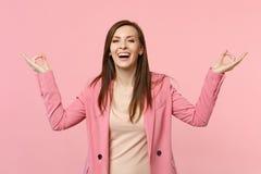 笑的滑稽的年轻女人在夹克在瑜伽姿态,被隔绝的放松的思考的举行手上在粉红彩笔墙壁 免版税库存图片