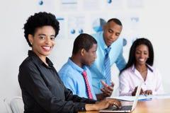 笑的非裔美国人的女实业家在工作在办公室 免版税库存照片