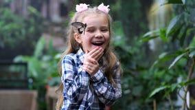 笑非常乐趣的美女 她有在她的面孔的一只蝴蝶 4K缓慢的mo 影视素材