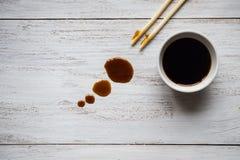 筷子和酱油在白色木桌上 免版税图库摄影