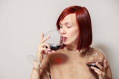 米黄礼服的年轻可爱的红发女孩斟酒服务员有明亮的唇膏的拿着并且尝试杯红酒并且估计芳香 库存图片
