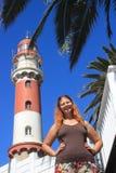 红发愉快的白白种人女孩在灯塔旁边站立在斯瓦科普蒙德纳米比亚和快乐地微笑 免版税库存图片