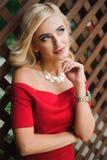 红色礼服的年轻可爱的女性白肤金发的妇女坐椅子 免版税库存图片