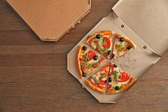 纸板箱用在木背景,顶视图的鲜美比萨 库存图片