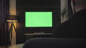绿色屏幕-人看着电视在客厅 在肩膀射击 影视素材
