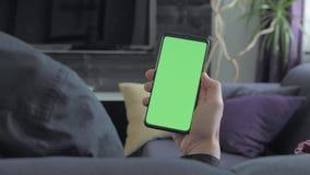 绿色屏幕-拿着智能手机的人 在肩膀视图 股票录像