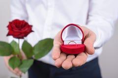 结婚提议概念 播种的特写镜头照片开放与美好的金黄圆环有大石头被隔绝的灰色背景 库存图片