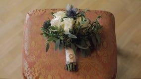 结婚戒指在椅子放置的美丽的婚姻的花束说谎 影视素材