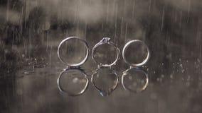 结婚戒指和说谎黑暗的水表面上的定婚戒指发光与宏指令的轻的关闭 3d背景回报飞溅空白的水 雨 股票录像