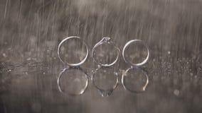 结婚戒指和说谎黑暗的水表面上的定婚戒指发光与宏指令的轻的关闭 3d背景回报飞溅空白的水 雨 影视素材
