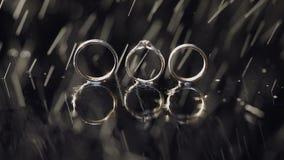 结婚戒指和说谎黑暗的水表面上的定婚戒指发光与宏指令的轻的关闭 3d背景回报飞溅空白的水 下雨下落 股票录像