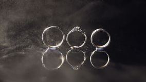 结婚戒指和说谎黑暗的水表面上的定婚戒指发光与光 关闭宏指令 在水对的圆环 股票视频