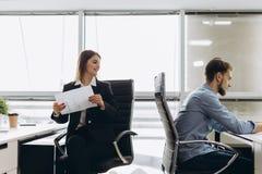 给纸的微笑的女实业家某人在办公室 免版税库存照片
