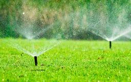 给绿草喝水的自动草坪喷水隆头 有自动化系统的喷水隆头 庭院灌溉系统浇灌的草坪 水 免版税库存图片