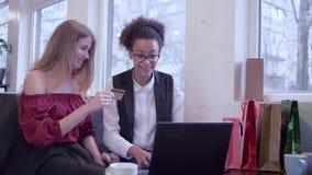 网上付款,愉快的混合的族种朋友为薪水坐互联网的购买使用信用卡和手提电脑在咖啡馆 股票视频