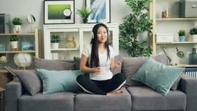 美丽的亚裔女孩听音乐通过耳机和跳舞的移动的手和身体在家坐沙发 影视素材