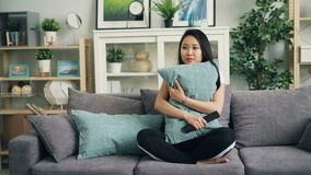 美丽的亚裔年轻女人在家观看在拿着枕头和然后起反应对可怕情节的电视的恐怖电影 股票录像