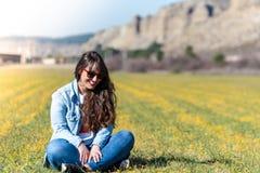 美丽的少女坐室外的草 库存图片