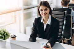 美丽的年轻和成功的微笑的女孩坐在桌上在她的办公室 女实业家 免版税库存图片