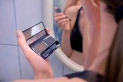 美丽的深色的妇女在镜子前面的卫生间里绘眼眉 回到视图 库存图片