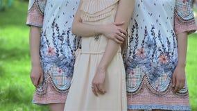 美丽的穿礼服和紧挨着站立户外在公园的新娘和女傧相 新娘,婚礼那天 股票视频