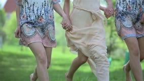 美丽的穿礼服和紧挨着赤足跑户外在公园的新娘和女傧相 新娘,婚礼那天 股票录像