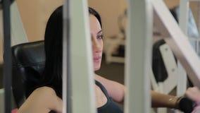 美丽的运动的深色的妇女订婚胸口和胳膊的肌肉的一台模拟器 生活方式概念 股票录像