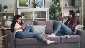 美女女学生在舱内甲板使用拿着小配件和触摸屏的智能手机坐沙发 股票视频