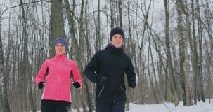 美女和一个人在冬天适当的营养和一种健康生活方式的森林里跑 慢的行动 股票视频