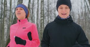 美女和一个人在冬天适当的营养和一种健康生活方式的森林里跑 慢的行动 股票录像