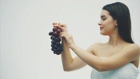 美女稀薄吃健康果子 拿着成熟葡萄花束的一俏丽的年轻女人的画象和真实 股票录像
