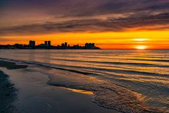 美好的橙色日落,城市剪影照片在海的日出的在海滨,平安的风景,下来太阳 库存照片