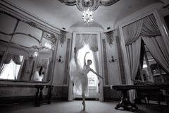 美好的芭蕾舞女演员跳舞在有枝形吊灯和镜子的一个豪华大厅里 免版税库存照片