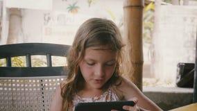 美好逗人喜爱白种人女孩儿童坐不耐烦在夏天咖啡馆大阳台桌上使用智能手机娱乐应用程序 股票录像