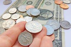 美国处所,角钱硬币在手中在美元美国背景 图库摄影