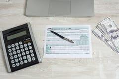 美国在计算机膝上型计算机、美金、计算器和报税表旁边的报税表1040 报税表我们营业收益办公室手 图库摄影
