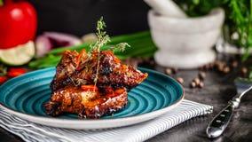 美国烹调 Grilled用了卤汁泡在一块蓝色板材的排骨用虾和辣辣椒在烤肉汁 背景概念能源图象 库存图片